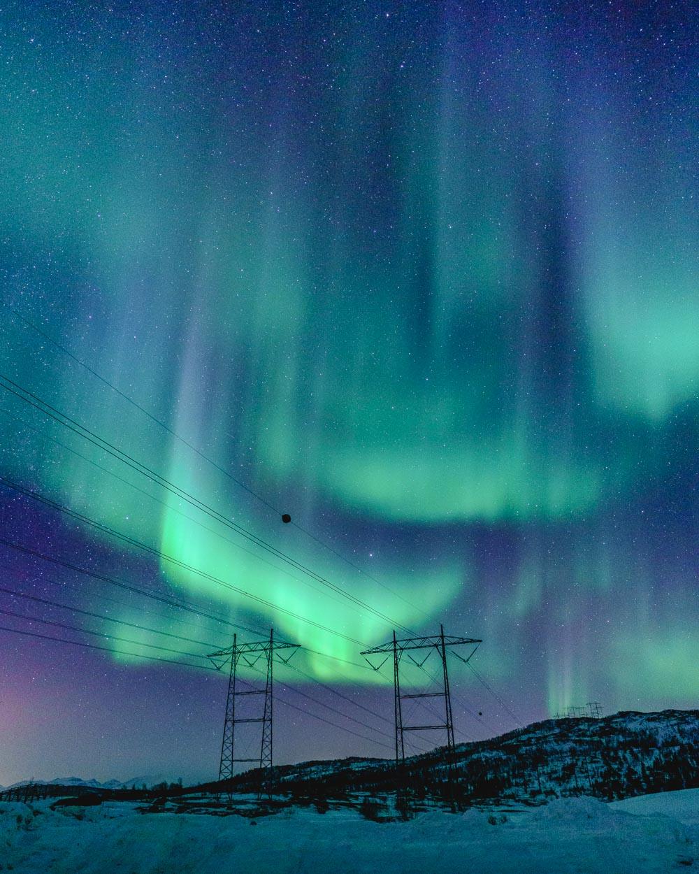 Nordlys som danser over høyspentledningene